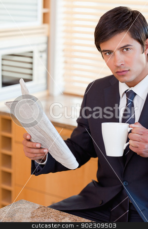 Portrait of a businessman drinking tea while reading a newspaper stock photo, Portrait of a businessman drinking tea while reading a newspaper in his kitchen by Wavebreak Media