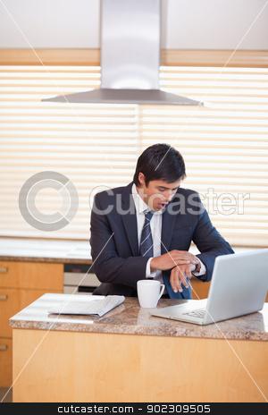 Portrait of a businessman running late stock photo, Portrait of a businessman running late in his kitchen by Wavebreak Media