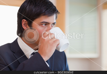 Close up of a businessman drinking tea stock photo, Close up of a businessman drinking tea in his kitchen by Wavebreak Media