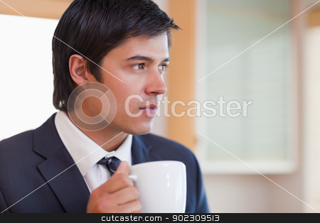 Close up of a handsome businessman drinking tea stock photo, Close up of a handsome businessman drinking tea in his kitchen by Wavebreak Media