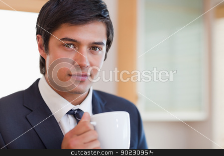 Close up of a handsome businessman drinking coffee stock photo, Close up of a handsome businessman drinking coffee in his kitchen by Wavebreak Media