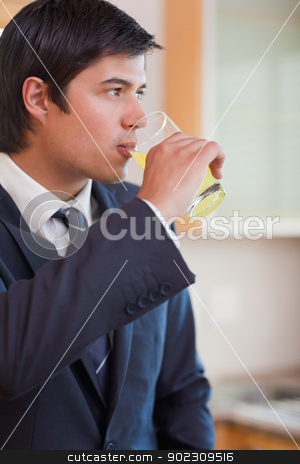 Portrait of a young businessman drinking orange juice stock photo, Portrait of a young businessman drinking orange juice in his kitchen by Wavebreak Media