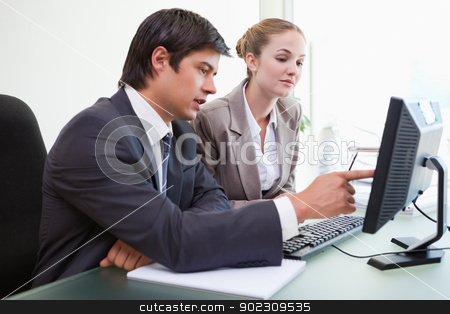 Good looking business people working with a computer stock photo, Good looking business people working with a computer in an office by Wavebreak Media