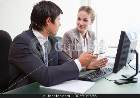 Business team working with a computer stock photo, Business team working with a computer in an office by Wavebreak Media