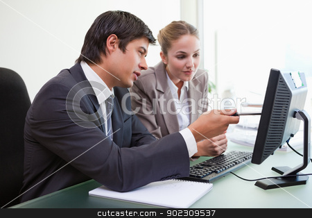 Focused business team working with a computer stock photo, Focused business team working with a computer in an office by Wavebreak Media