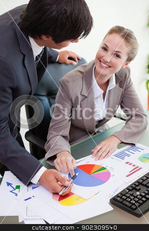 Portrait of a smiling business team studying statistics stock photo, Portrait of a smiling business team studying statistics in a meeting room by Wavebreak Media