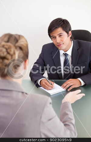 Portrait of a smiling manager interviewing a female applicant stock photo, Portrait of a smiling manager interviewing a female applicant in an office by Wavebreak Media