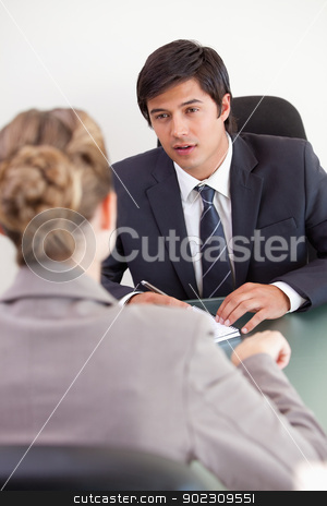 Portrait of a serious manager interviewing a female applicant stock photo, Portrait of a serious manager interviewing a female applicant in his office by Wavebreak Media