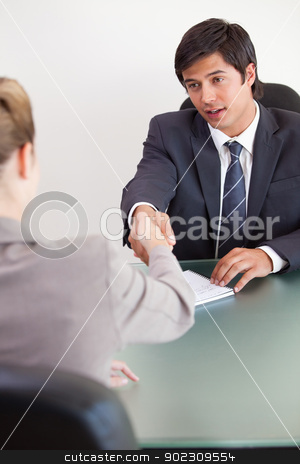 Portrait of a manager shaking the hand of a customer stock photo, Portrait of a manager shaking the hand of a customer in his office by Wavebreak Media