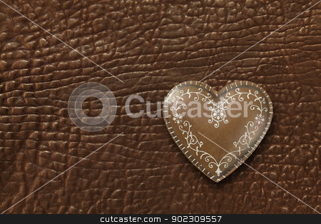 Heart on leather background stock photo, Photo of a metal heart on a dark brown leather background. by © Ron Sumners