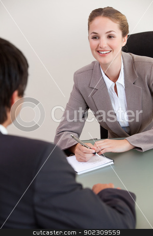 Portrait of a smiling manager interviewing a male applicant stock photo, Portrait of a smiling manager interviewing a male applicant in her office by Wavebreak Media
