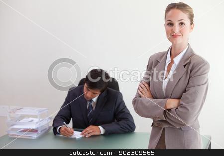 Young busineswosman posing while her colleague is working stock photo, Young busineswosman posing while her colleague is working in an office by Wavebreak Media