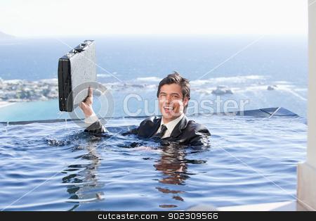 Businessman holding a briefcase stock photo, Businessman holding a briefcase in a swimming pool by Wavebreak Media