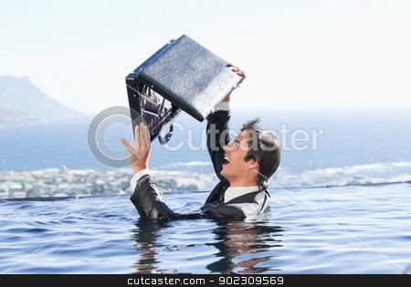 Businessman looking in his briefcase stock photo, Businessman looking in his briefcase in a swimming pool by Wavebreak Media