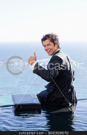 Portrait of a businessman with the thumb up stock photo, Portrait of a businessman with the thumb up in a swimming pool by Wavebreak Media