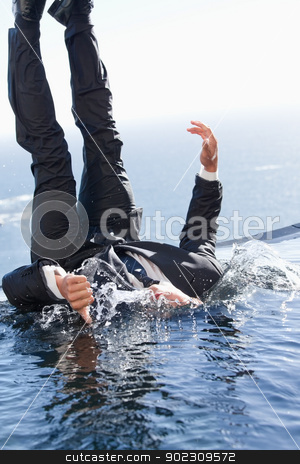 Portrait of a cheerful businessman falling into water stock photo, Portrait of a cheerful businessman falling into water with the thumb up by Wavebreak Media
