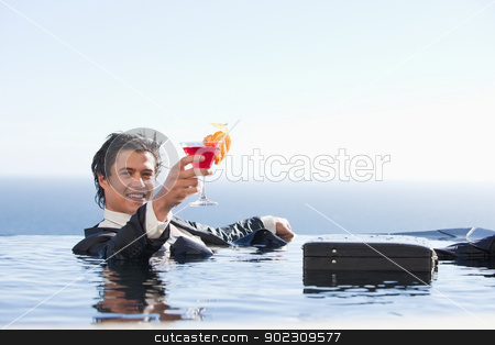 Cheerful businessman relaxing in a swimming pool with a cocktail stock photo, Cheerful businessman relaxing in a swimming pool with a cocktail in a suit by Wavebreak Media