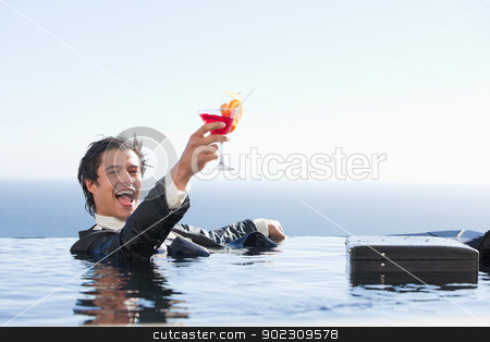 Delighted businessman relaxing in a swimming pool with a cocktai stock photo, Delighted businessman relaxing in a swimming pool with a cocktail in a suit by Wavebreak Media