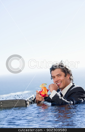Portrait of a smiling businessman relaxing in a swimming pool wi stock photo, Portrait of a smiling businessman relaxing in a swimming pool with a cocktail in a suit by Wavebreak Media