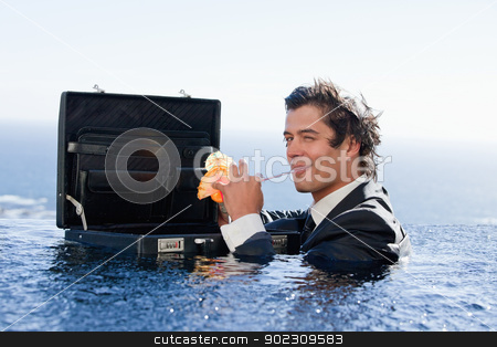 Businessman drinking a cocktail stock photo, Businessman drinking a cocktail in a swimming pool by Wavebreak Media