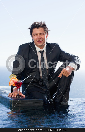 Portrait of a businessman posing with a cocktail in a briefcase stock photo, Portrait of a businessman posing with a cocktail in a briefcase in a swimming pool by Wavebreak Media