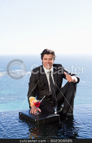 Portrait of a businessman posing with a cocktail on a briefcase stock photo, Portrait of a businessman posing with a cocktail on a briefcase with the thumb up by Wavebreak Media