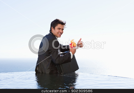 Portrait of a businessman posing with a cocktail and a briefcase stock photo, Portrait of a businessman posing with a cocktail and a briefcase in a swimming pool by Wavebreak Media