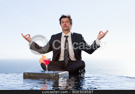 Businessman relaxing in the lotus position stock photo, Businessman relaxing in the lotus position with a cocktail in a swimming pool by Wavebreak Media