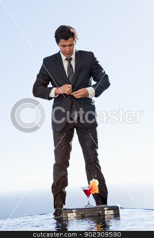Portrait of a businessman standing up outside a swimming pool stock photo, Portrait of a businessman standing up outside a swimming pool with a cocktail by Wavebreak Media