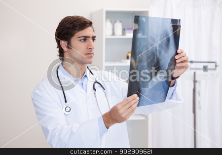 Male doctor looking at x-ray stock photo, Young male doctor looking at x-ray by Wavebreak Media