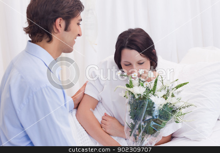 Man brought flowers to his girlfriend in the hospital stock photo, Young man brought flowers to his girlfriend in the hospital by Wavebreak Media