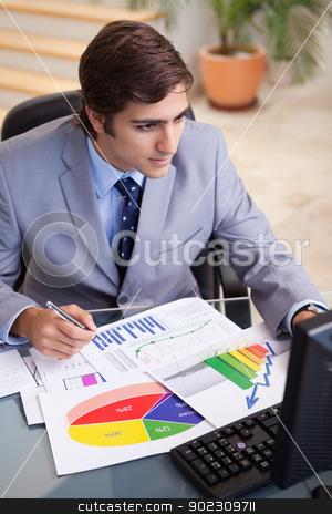Businessman analyzing statistics at his desk stock photo, Young businessman analyzing statistics at his desk by Wavebreak Media