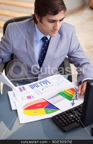 Businessman analyzing statistics at his computer stock photo, Young businessman analyzing statistics at his computer by Wavebreak Media