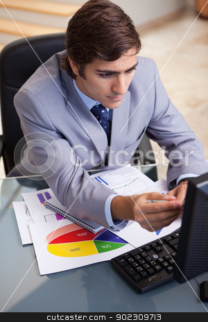 Businessman analyzing statistics stock photo, Young businessman analyzing statistics by Wavebreak Media