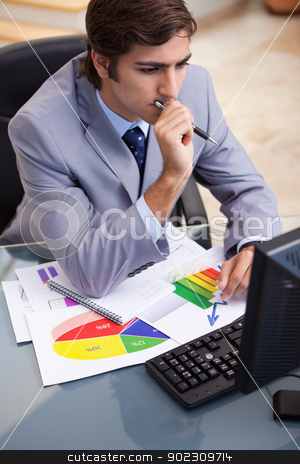 Businessman working on statistics at his desk stock photo, Young businessman working on statistics at his desk by Wavebreak Media