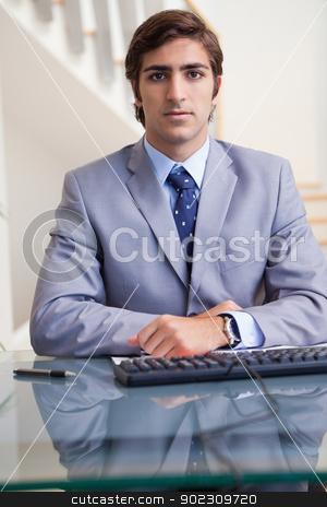 Businessman sitting behind his desk stock photo, Young businessman sitting behind his desk by Wavebreak Media