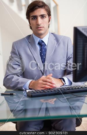 Businessman sitting behind his computer stock photo, Young businessman sitting behind his computer by Wavebreak Media