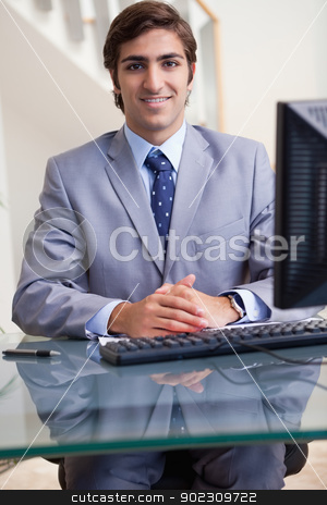 Smiling businessman sitting at his computer stock photo, Smiling young businessman sitting at his computer by Wavebreak Media