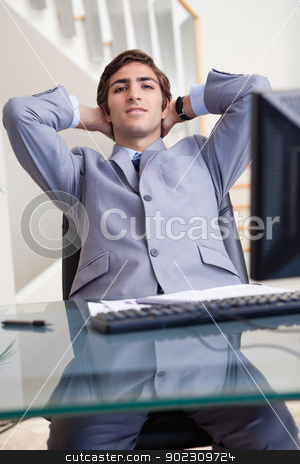 Businessman leaning back in his office stock photo, Young businessman leaning back in his office by Wavebreak Media