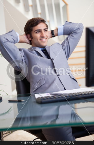 Smiling businessman leaning back in his office stock photo, Smiling young businessman leaning back in his office by Wavebreak Media
