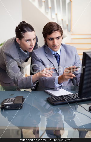 Businessman showing whats on his screen to his colleague stock photo, Young businessman showing whats on his screen to his colleagues by Wavebreak Media
