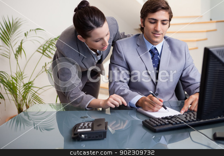 Businessman taking notes while getting mentored by colleague stock photo, Young businessman taking notes while getting mentored by colleague by Wavebreak Media