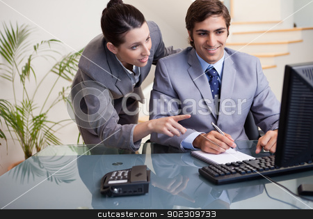 Businesswoman explaining her colleague what he has to do stock photo, Young businessman explaining her colleague what he has to do by Wavebreak Media