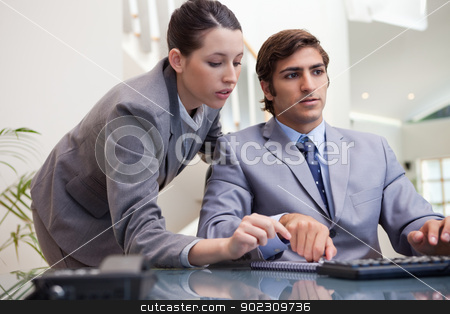 Business team working on pc together stock photo, Young business team working on pc together by Wavebreak Media