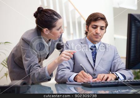 Businessman taking notes while getting explanation by colleague stock photo, Young businessman taking notes while getting explanation by colleague by Wavebreak Media