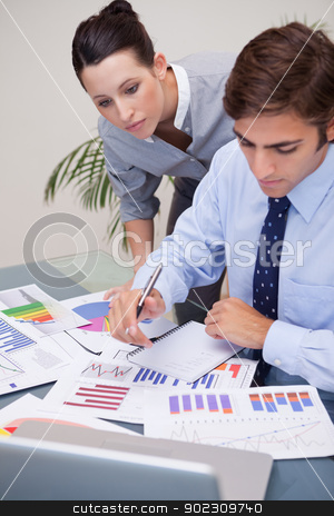 Business team analyzing statistics together stock photo, Young business team analyzing statistics together by Wavebreak Media