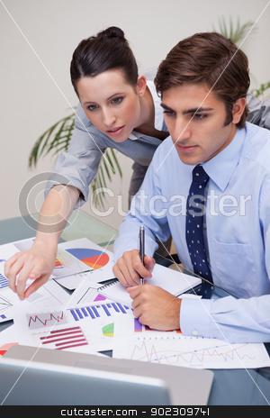Business team working on statistics together stock photo, Young business team working on statistics together by Wavebreak Media