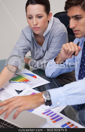 Business team analyzing charts together stock photo, Young business team analyzing charts together by Wavebreak Media