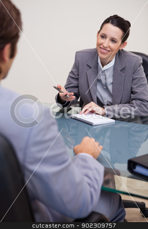 Smiling businesswoman with notepad in negotiation stock photo, Smiling young businesswoman with notepad in negotiation by Wavebreak Media