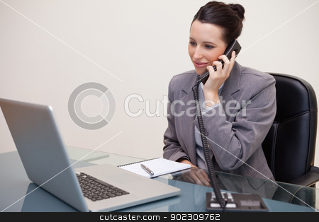 Smiling businesswoman on the telephone stock photo, Smiling young businesswoman on the telephone by Wavebreak Media